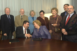 Deans and officials look on as Interim President Philip and Rector Shaidenko shake hands on the agreement.
