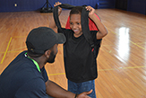 Psychology student speaking with a young boy at the Schenectady Boys & Girls Club.