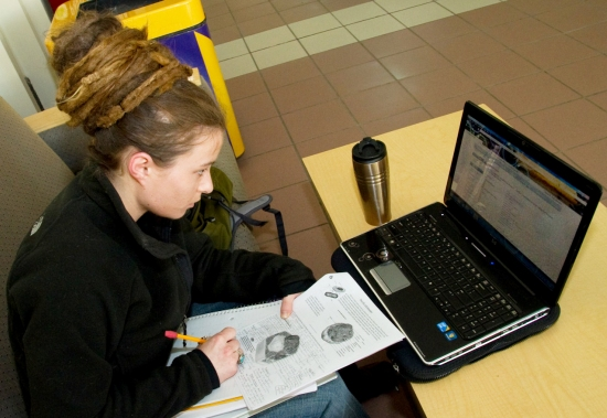 UAlbany student Emma Cerasoli sitting in front of her laptop in the Campus Center
