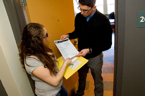 A UAlbany student hands out a census form to another UAlbany student in a door way.