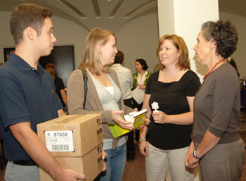 UAlbany sustainability director Mary Ellen Mallia hands out CFL light bulbs with students