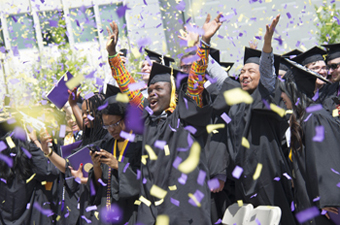 UAlbany students in caps and gowns celebrate graduation with purple and gold confetti