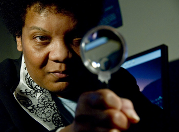 UAlbany criminologist Frankie Bailey peers through a magnifying glass.