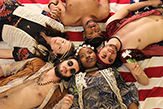 Five cast members lying on the floor in a circle with heads touching