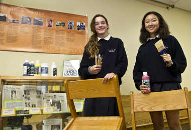 Holy Names students Kerry Losert and Stella Hong prepare to paint UAlbany library chairs.