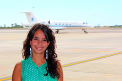UAlbany doctoral student Rosimar Rios-Berrios standing in front of the G-IV aircraft.