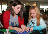 A CNSE staff member helps a visitor at CNSE Community Day