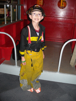 Boy dressed in fireman's attire during Center for Autism and Related Disabilities activity