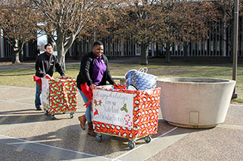 a woman pushes a cart full of gifts at UAlbany