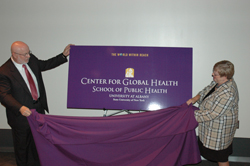 UAlbany School of Public Health Dean Philip Nasca and Center for Global Health Director Carol Whittaker unveil the banner for the new center devoted to addressing the world's health issues.