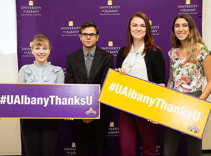 Students hold #UAlbanyThanksU signs to show their gratitude