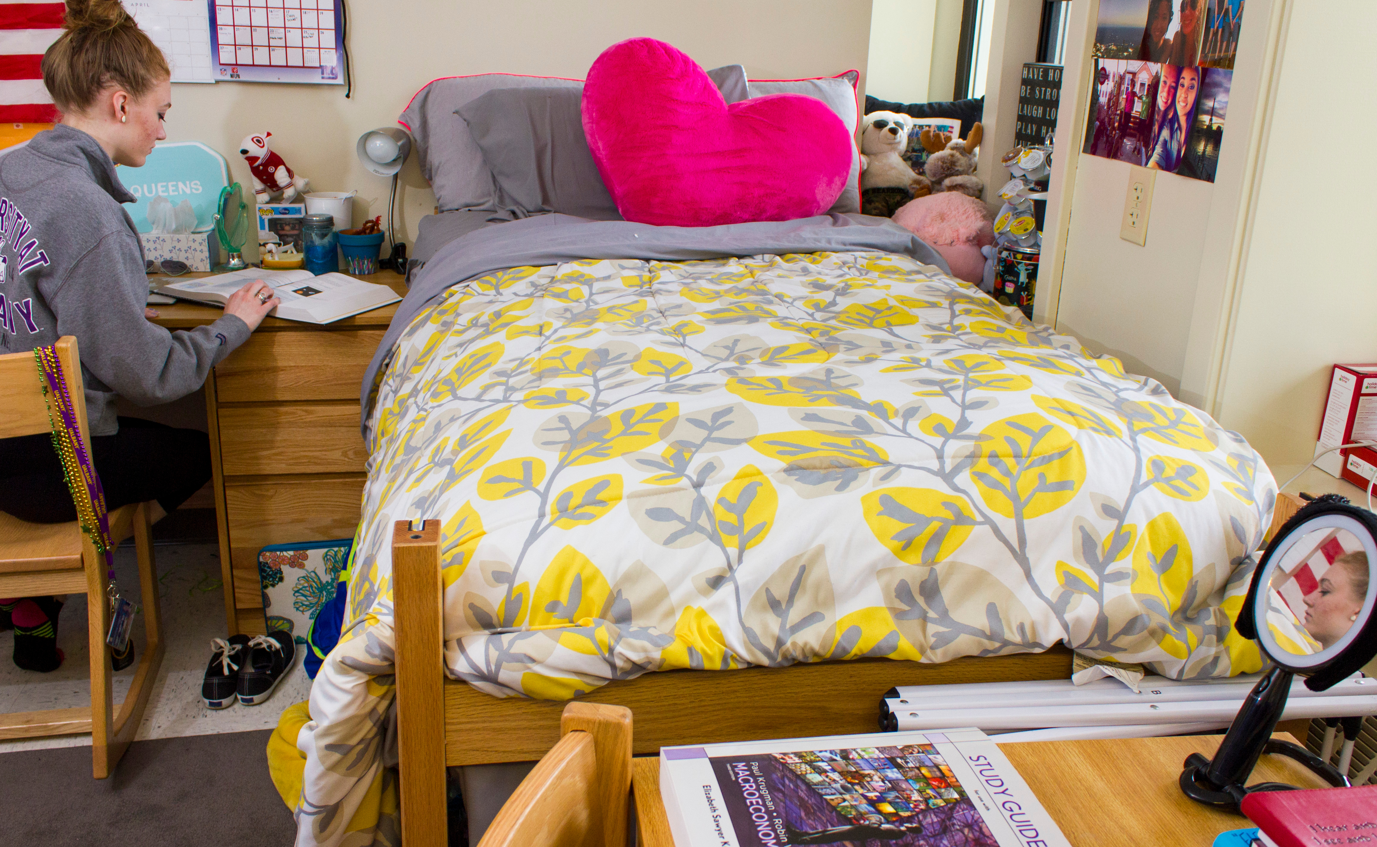 A student reads a textbook inside her residence hall bedroom