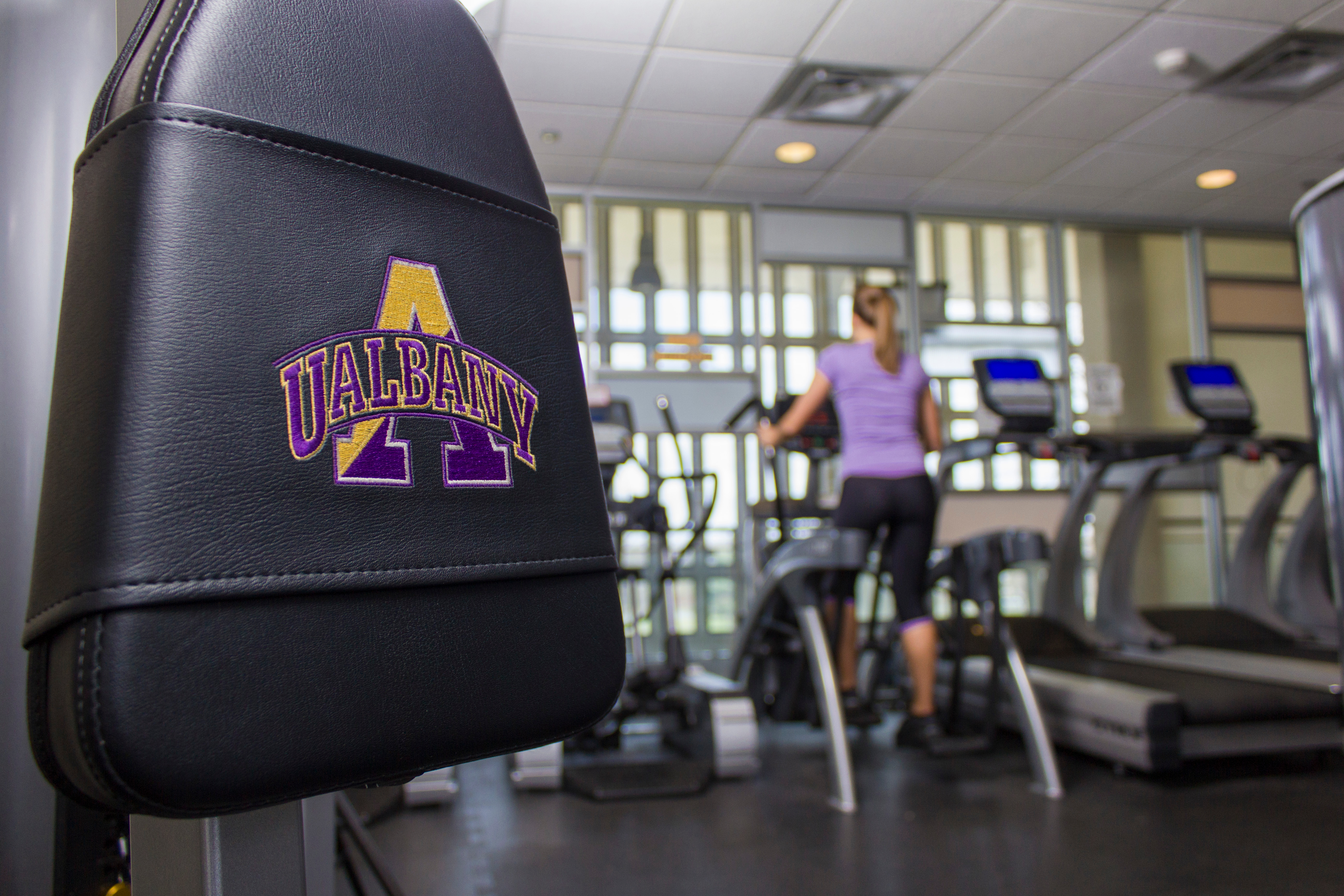 A student uses an elliptical machine inside a fitness center