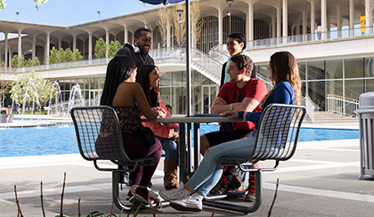 Six students gathered around a table in front of the UAlbany main fountain