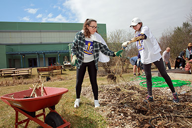 Two students clear a garden bed during a community service event