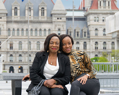 Michelle and her mom take a picture in downtown Albany at the capital.