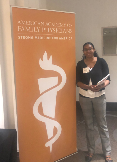 Elizabeth S. stands next to a orange pop-up banner that displays the name of the conference she attended. The conference logo, a white triangle with a squiggle on top, is also on the poster.