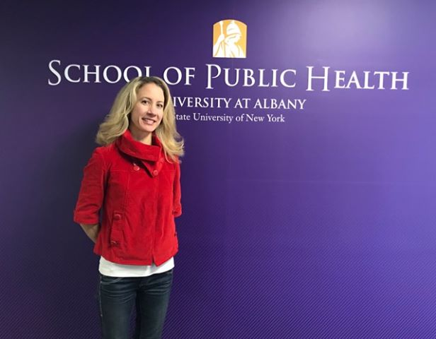 Meg V. stands against a purple wall with the School of Public Health logo on it. She is wearing a red sweater and blue jeans and is smiling at the camera.