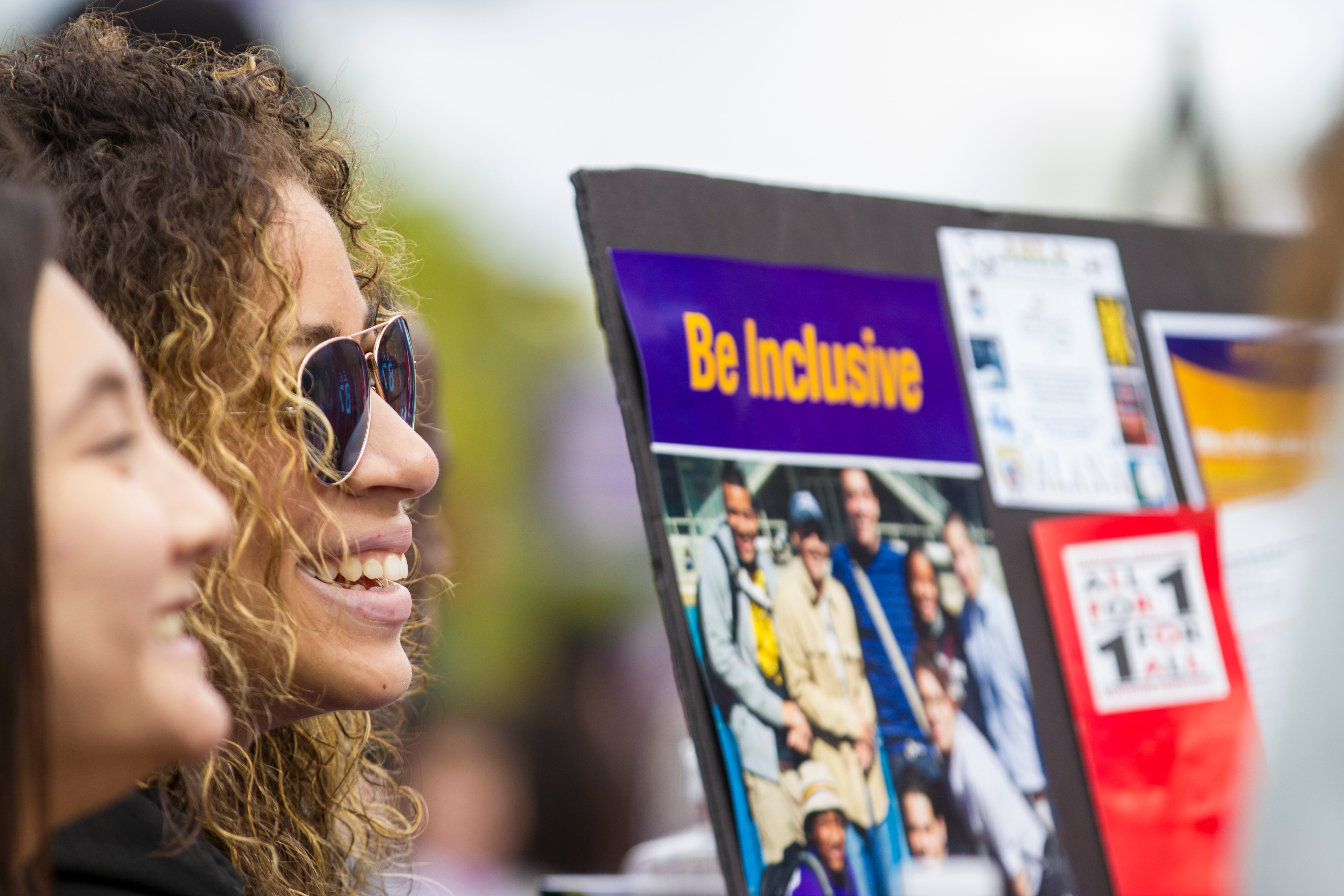 "Two students table during the Student Affairs Block Party, smiling beside a poster that says ""Be Inclusive"""