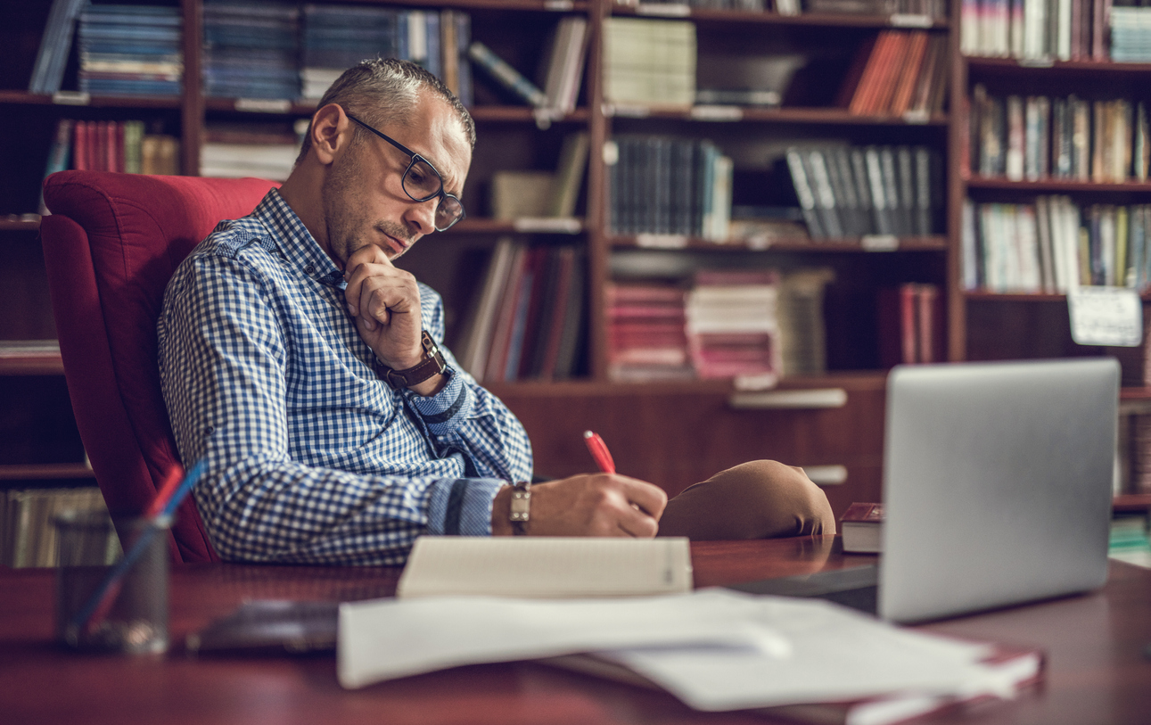 A man making notes in his home office