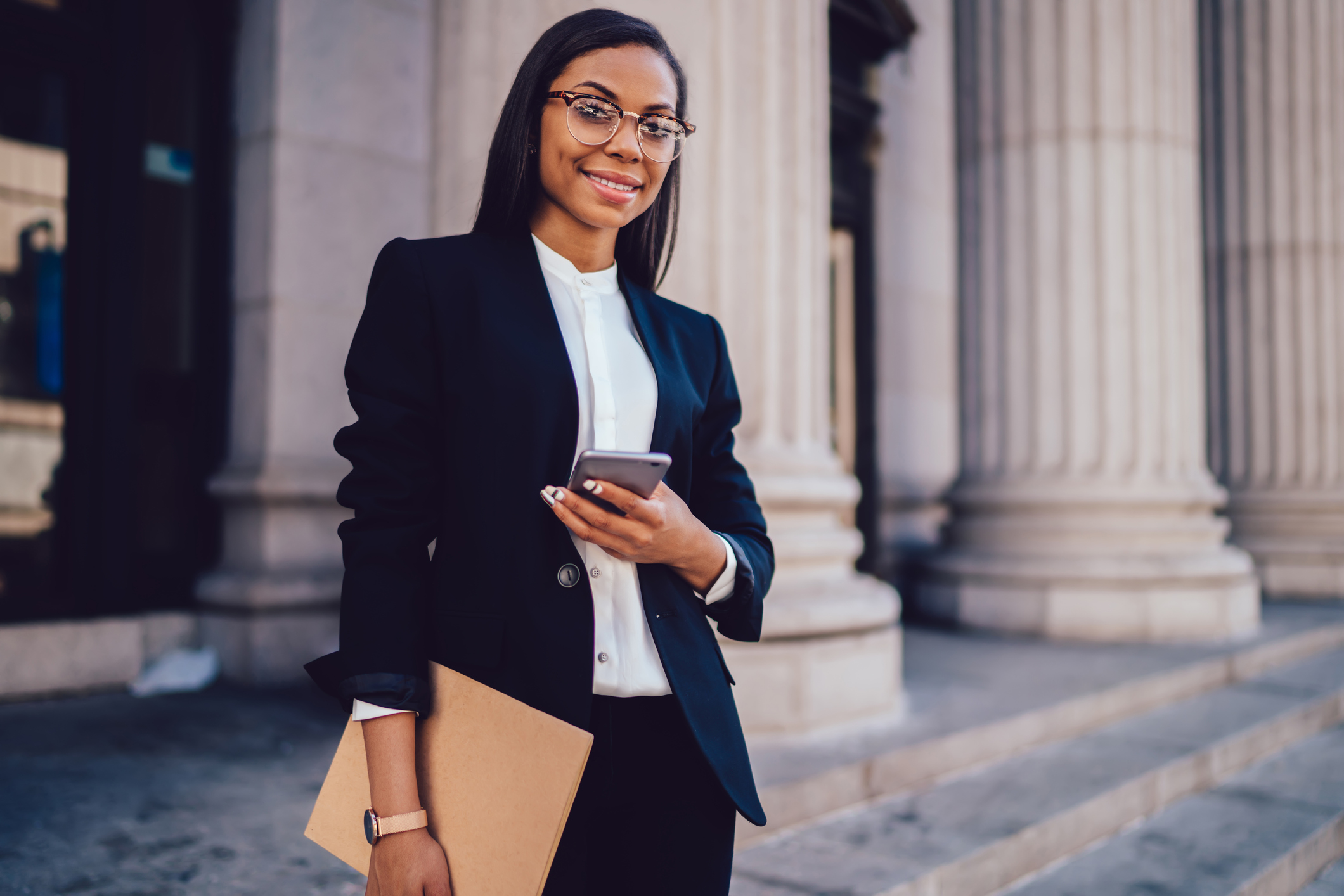 Young professional woman holding a folder and using a smartphone
