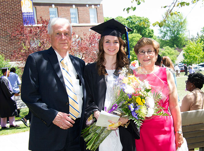 Parents celebrate with their daughter at UAlbany commencement ceremony