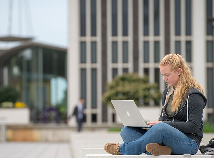 Student works on her computer outside on UAlbany's uptown campus