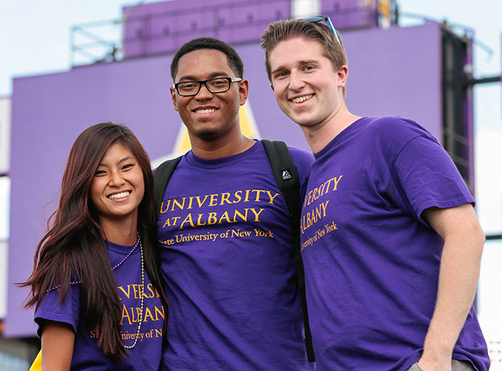 Three UAlbany students in purple t-shirts pose for a photo