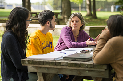 Students working with a professor on campus