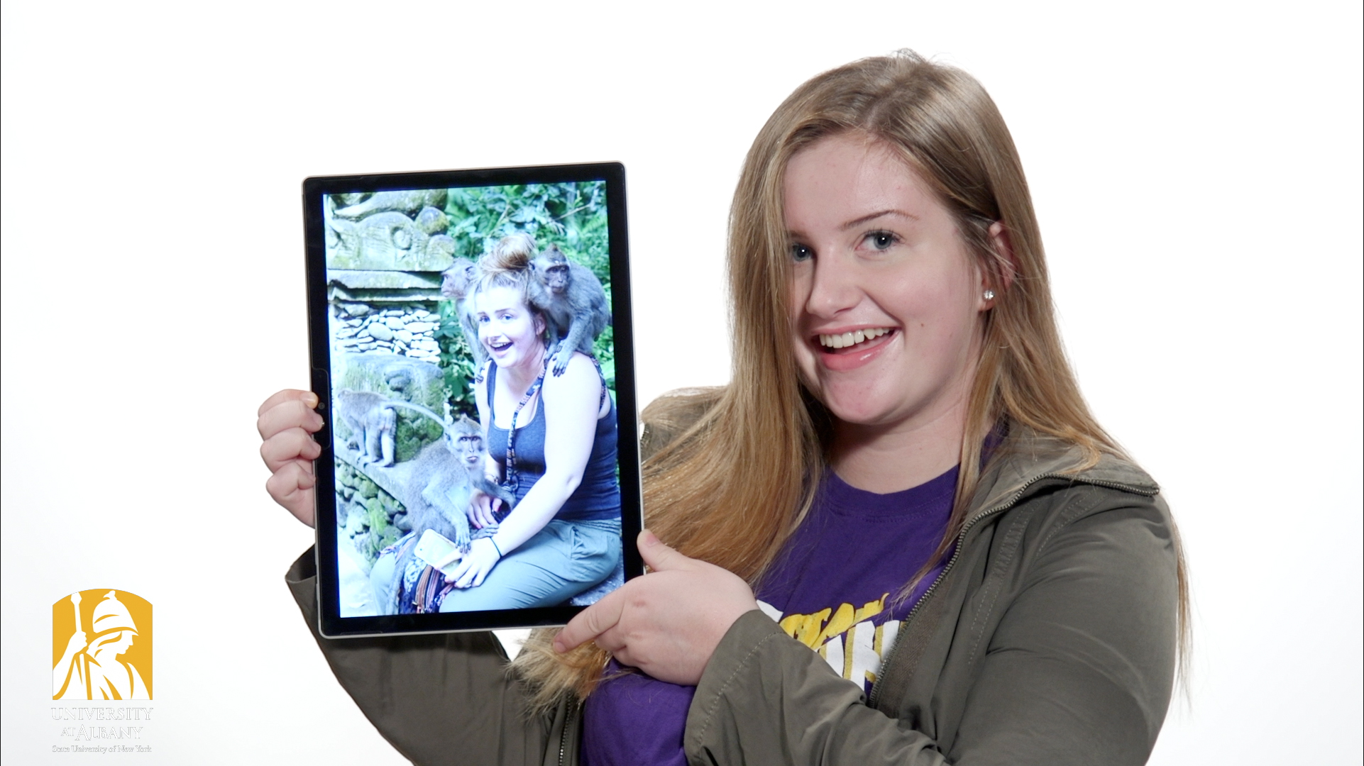 Woman holding a tablet showing a picture of herself with several monkeys climbing on her.