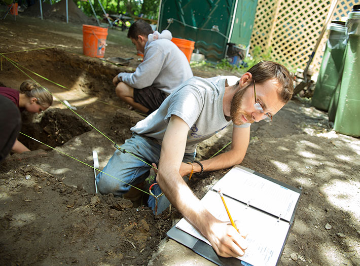 Student takes notes at archaeological dig