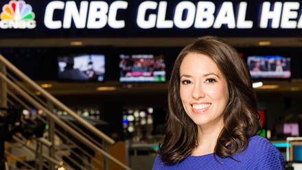 Stephanie Landsman standing in the CNBC studios with the CNBC logo
