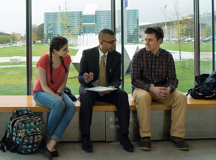 Students chat with professor in Massry Center for Business