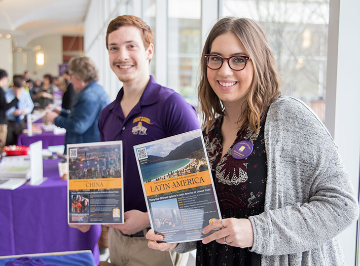 Students hold flyers for study abroad programs in Latin America and China