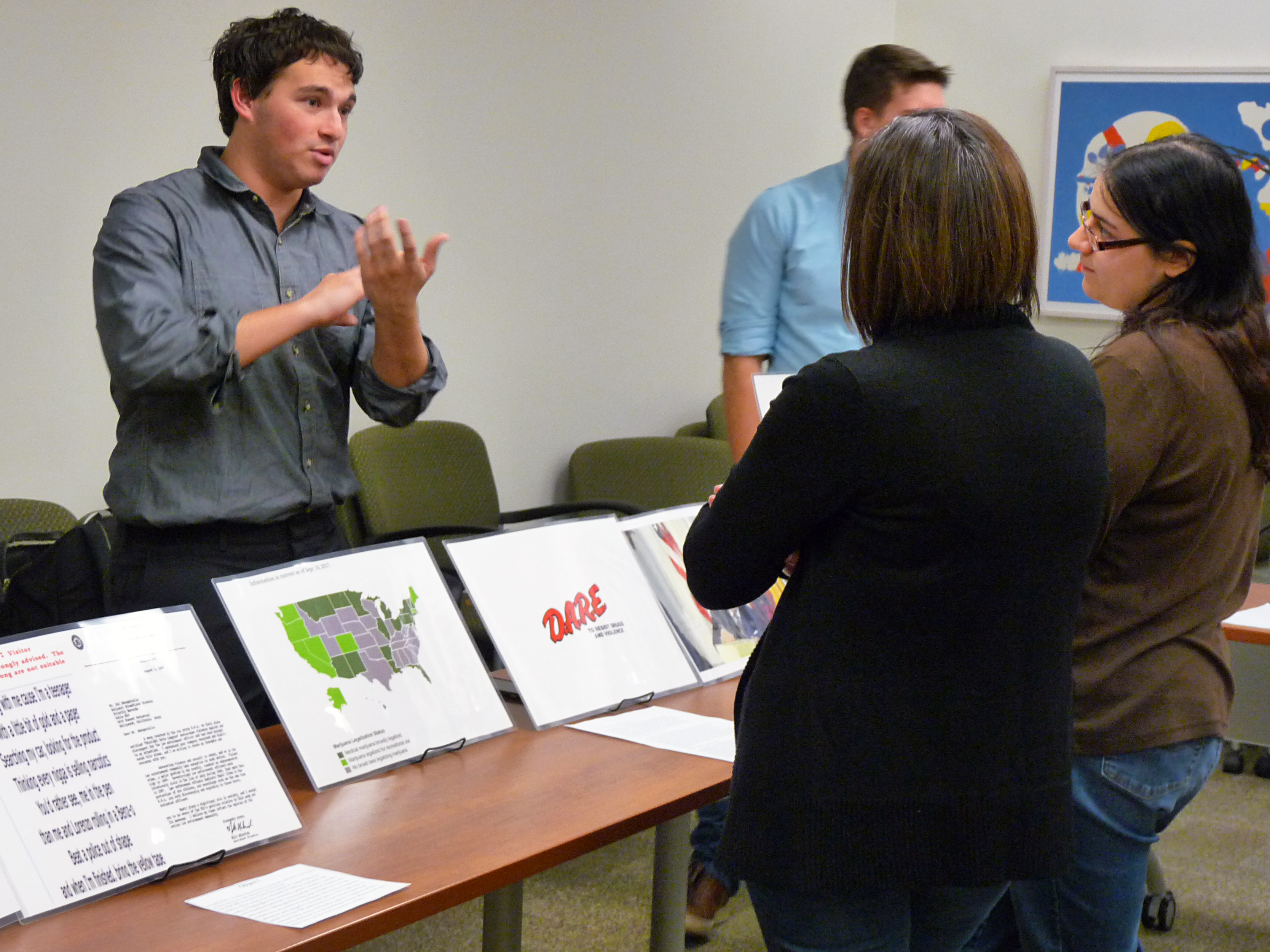 A student discusses his criminal justice research with community members