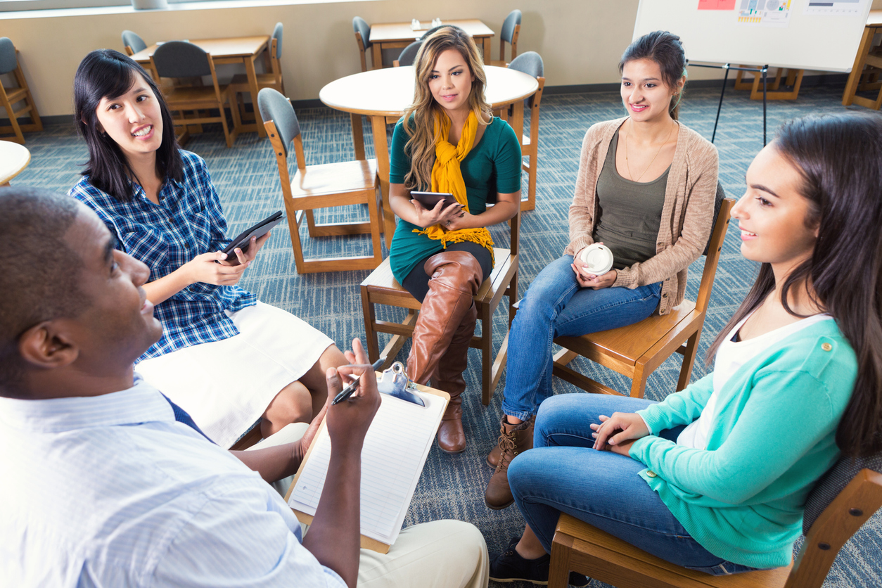 Five young adults in a group discussion