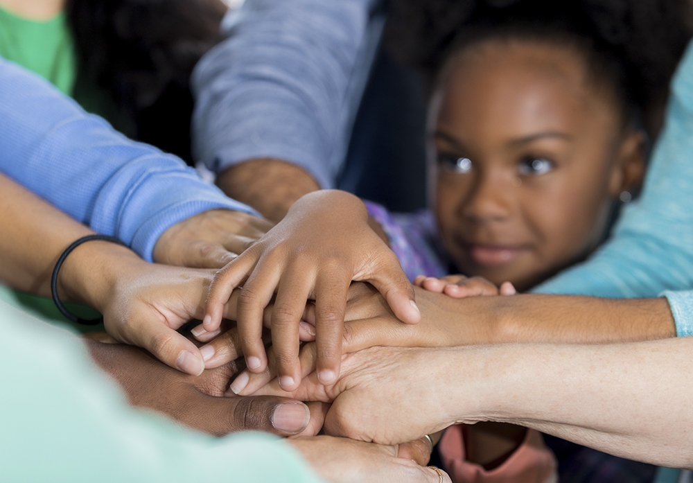 Several hands forming a group handshake with a young black child's face in the background