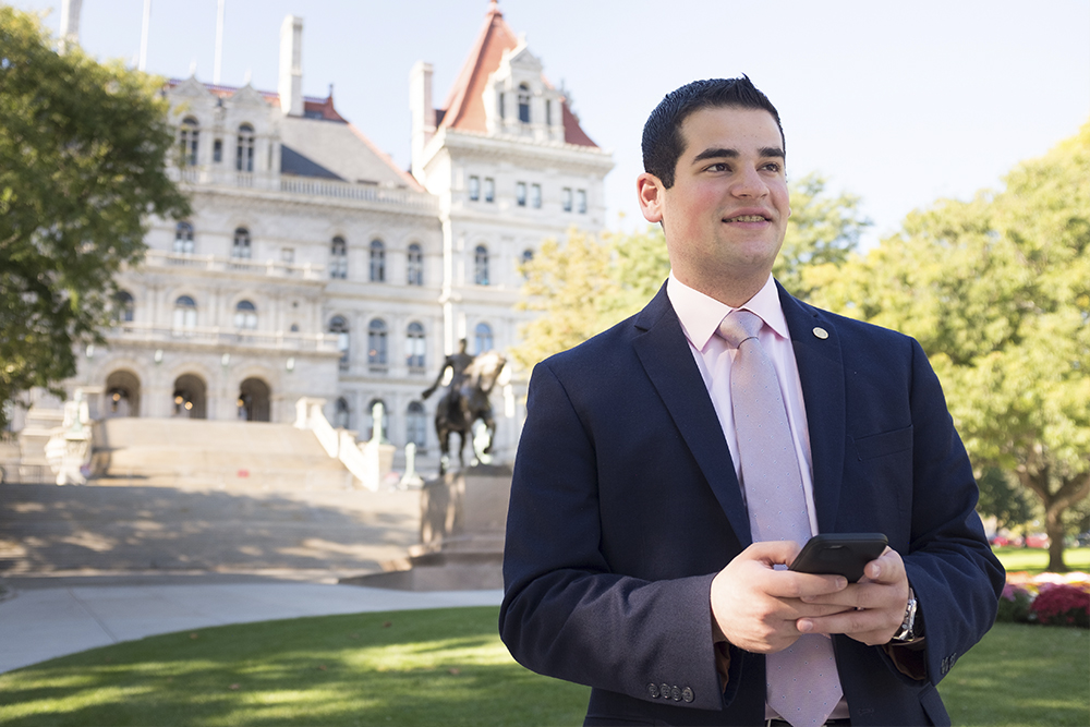 Student texting and standing in front of the NYS Capitol