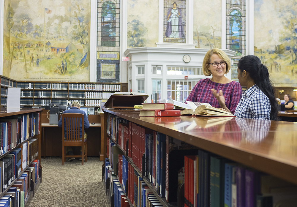 Students in the University at Albany's Dewey Library having a discussin at a reference shelf