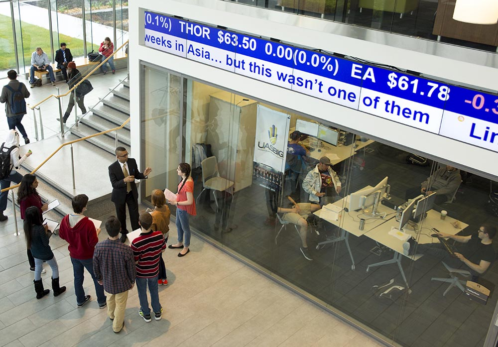 Students in the lobby of the University at Albany's School of Business, standing in front of a stock ticker