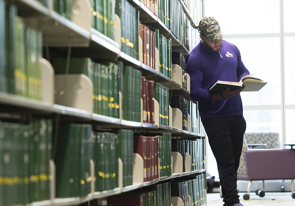 Student reading a book among the library stacks