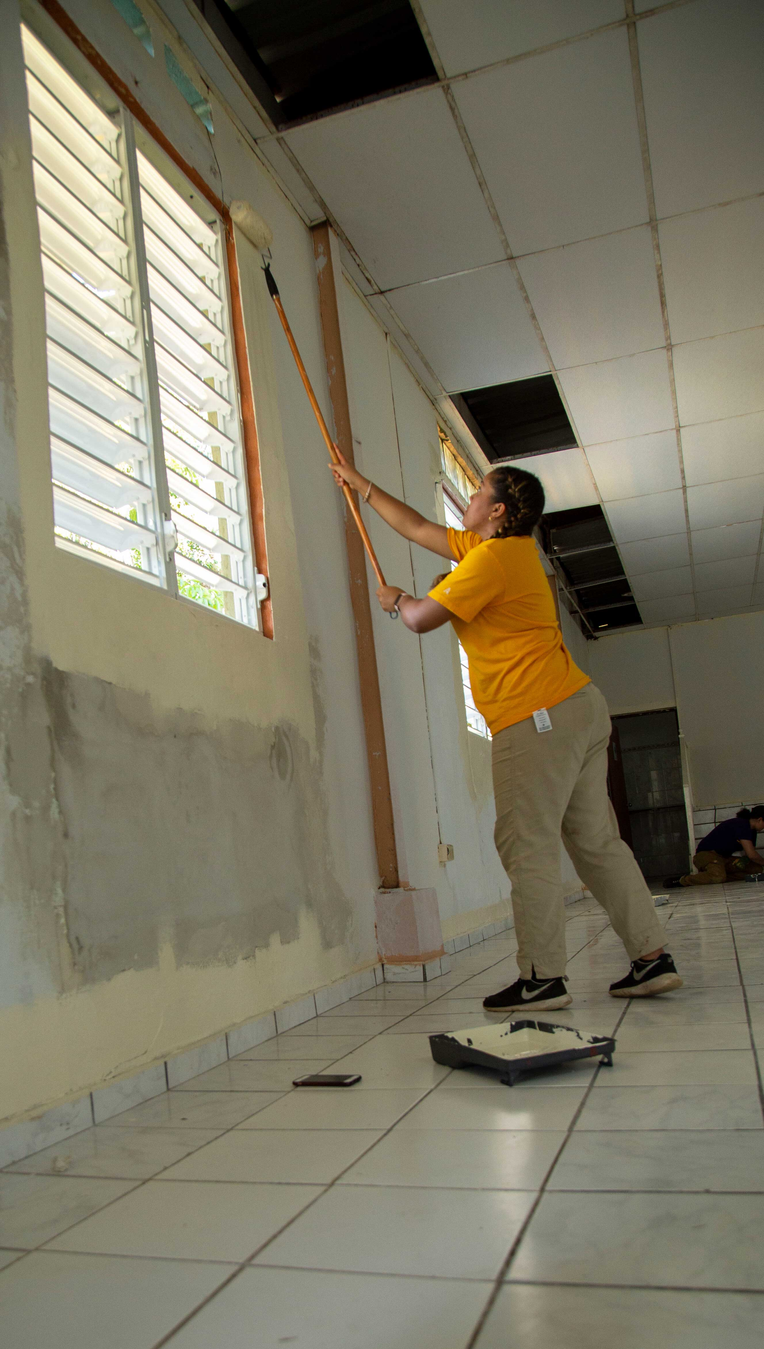 Student repainting a community center in Bayamon, Puerto Rico that was damaged by Hurricane Maria.