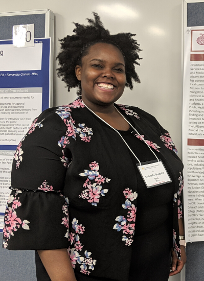 Gabby smiles at the camera, wearing a black top with pink flowers. She is standing in front of her academic poster displaying information from her internship experience.