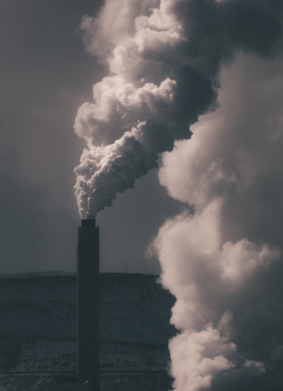 A dark image shows a factory emitting pollution from a tower.
