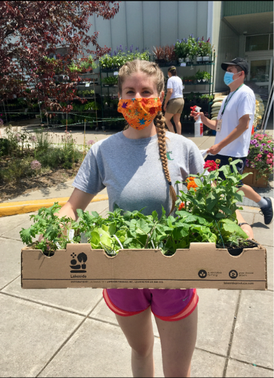Leanna K. holds a box of planted vegetables. She is wearing an orange face mask and stands outside a childcare center.