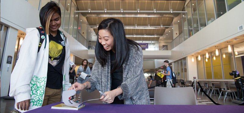 UAlbany Alum Awkwafina signing a book for a student