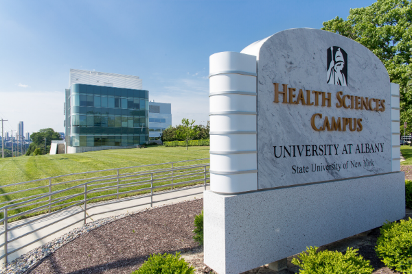"A marble sign says ""Health Sciences Campus"". Behind this, green grass, a bright blue sky, and a building can be seen."