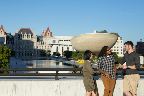 Three students stand talking. They are standing in front of the iconic downtown Albany view, with the Egg and the state building behind them.