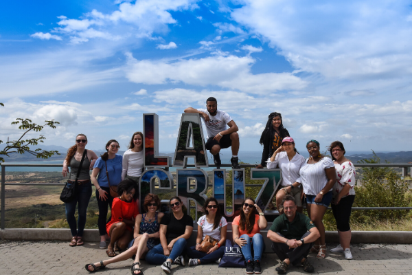 "A group of students stand in front of a sign saying ""La Cruz"". They are on a study abroad program."