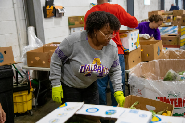 A student wearing a UAlbany shirt helps to organize food at the local food bank.